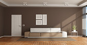 Brown and white living room with elegant sofa and closed door - 3d rendering Note: the room does not exist in reality, Property model is not necessary