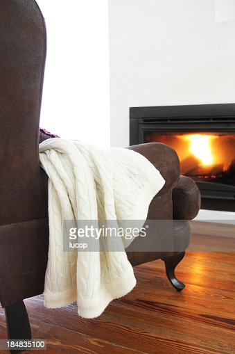 Brown armchair from the back in front of modern fireplace
