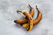 Three rotten brown bananas on a concrete table