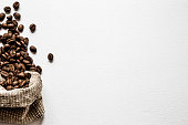 Brown beans with burlap bag on the white table. Harvest of coffee in different countries. Choice of the best sort and quality coffee. Empty place for a text. Web background.