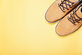 Top view of Brown boots on yellow background. Copyspace, flat lay. Traveling boots, minimalist.
