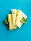 Brown bread with cheese and basil leaf on blue background