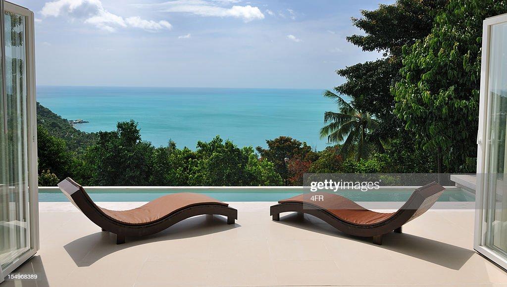 Brown chaises longues au bord de la piscine privée de la villa : Photo