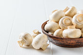 Brown clay bowl with mushrooms on white wooden table. Vegetarian cuisine. Natural plant food.