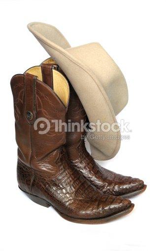 Botas de vaquero marrón y se sentía sombrero sobre fondo blanco   Foto de  stock 90a197ab064