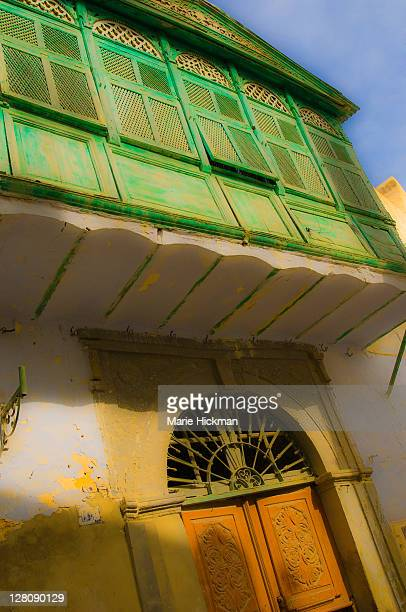 Brown entry door and green overhang with green shuttered windows in the streets of Kairouan, Tunisia