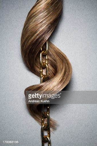 Brown hair wrapping curling around linked chain.