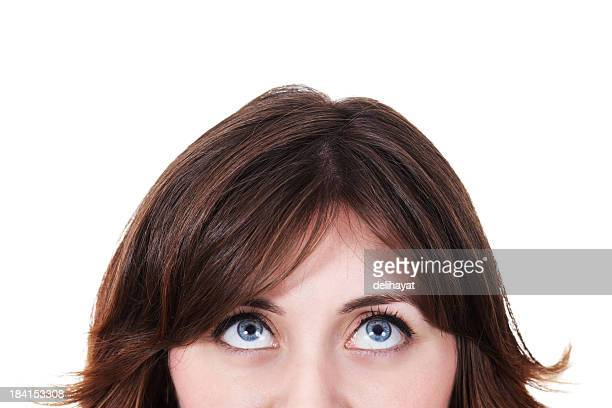 A brown haired woman looking up on a white background