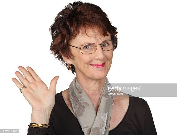 A brown haired woman with glasses waving with her right hand