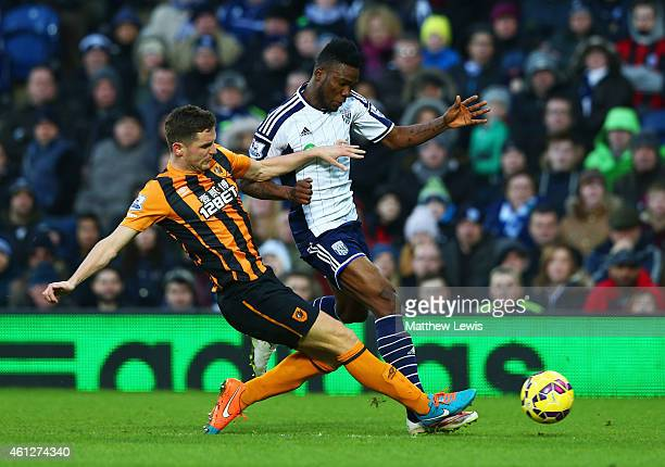 Brown Ideye of West Bromwich Albion is challenged by Alex Bruce of Hull City during the Barclays Premier League match between West Bromwich Albion...