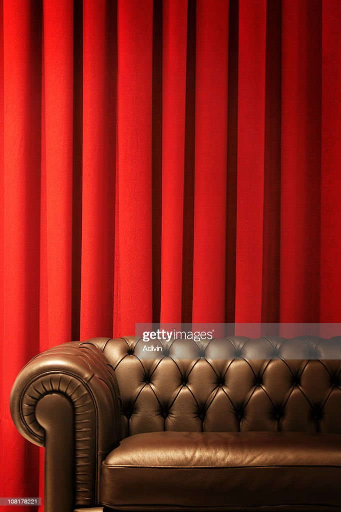 brown leather couch and red curtains stock photo getty