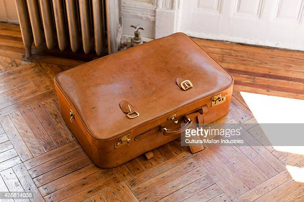 Brown leather suitcase on wooden floor