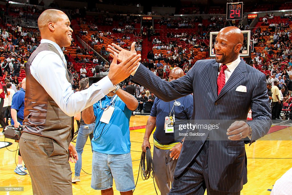 P.J. Brown, left, and Alonzo Mourning, former players with the Miami Heat, greet each other at halftime of a game between the Atlanta Hawks and Heat on March 12, 2013 at American Airlines Arena in Miami, Florida.