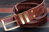Brown men leather belt with golden buckle over leather strips background