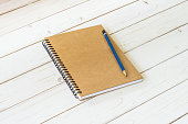 Brown notebook with blank pages and pencil on wood table
