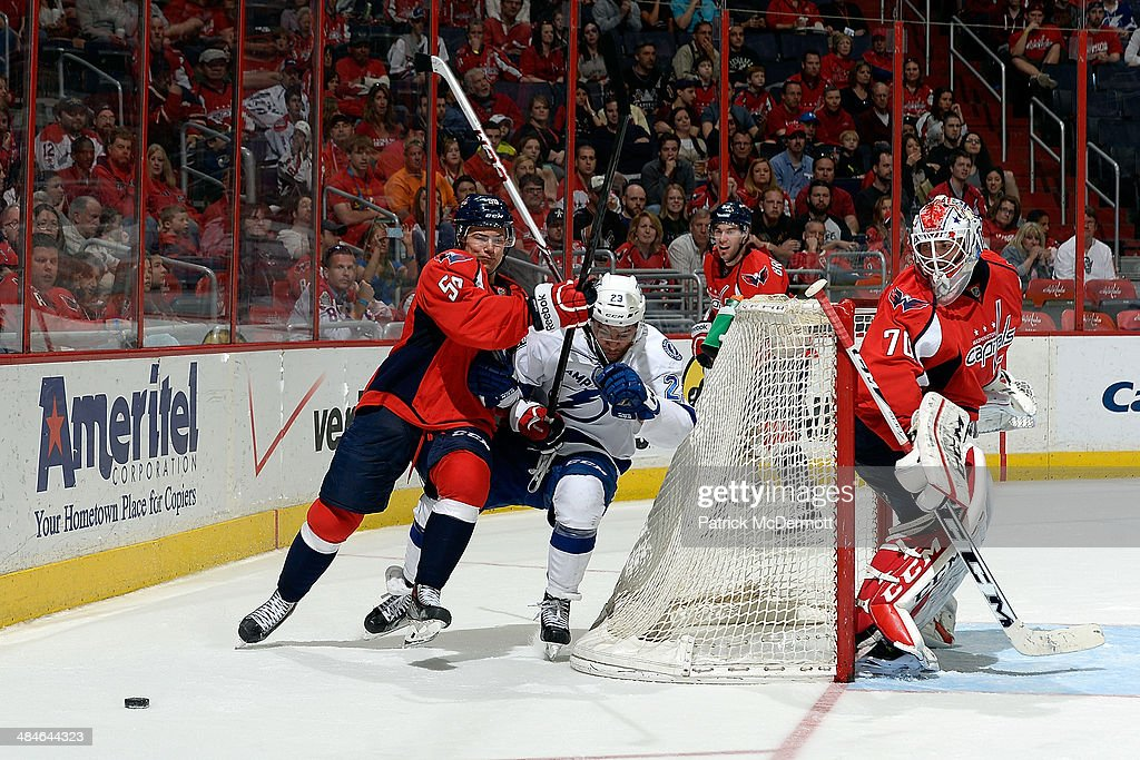 J.T. Brown #23 of the Tampa Bay Lightning and Connor Carrick #58 of the Washington Capitals battle for the puck behind the net in the third period during an NHL game at Verizon Center on April 13, 2014 in Washington, DC.