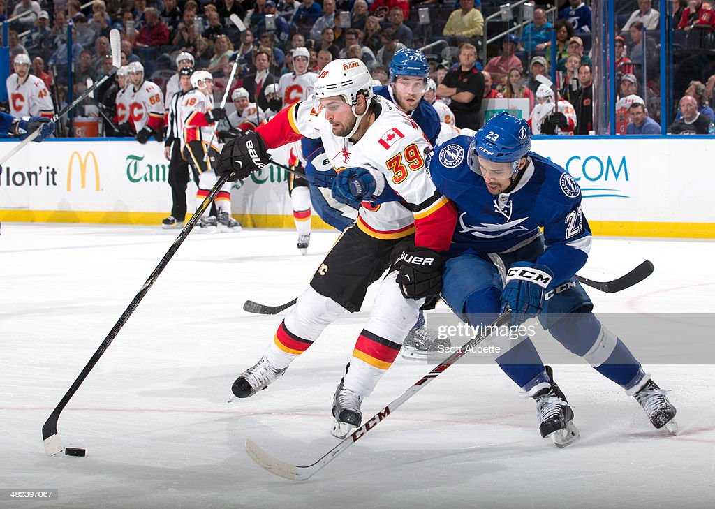 J.T. Brown #23 of the Tampa Bay Lightning battles for the puck against <a gi-track='captionPersonalityLinkClicked' href=/galleries/search?phrase=T.J.+Galiardi&family=editorial&specificpeople=4324979 ng-click='$event.stopPropagation()'>T.J. Galiardi</a> #39 of the Calgary Flames during the second period at the Tampa Bay Times Forum on April 3, 2014 in Tampa, Florida.