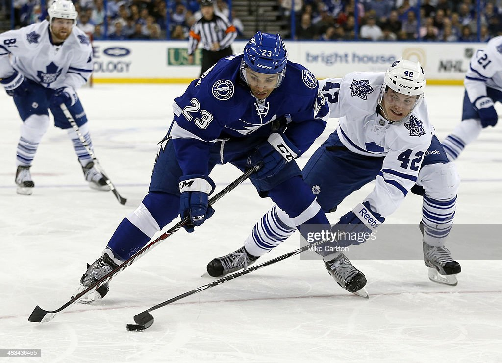 J.T. Brown #23 of the Tampa Bay Lightning is checked by Tyler Bozak #42 of the Toronto Maple Leafs at the Tampa Bay Times Forum on April 8, 2014 in Tampa, Florida.