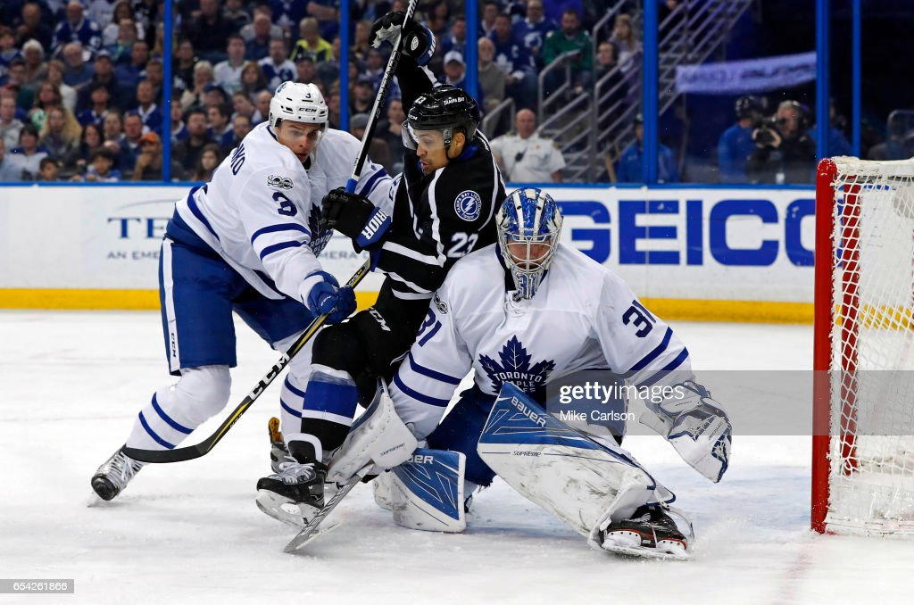 J.T. Brown #23 of the Tampa Bay Lightning is sandwiched between Alexey Marchenko #3 and Frederik Andersen #31 of the Toronto Maple Leafs during the second period at the Amalie Arena on March 16, 2017 in Tampa, Florida.