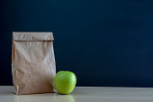 School lunch. Brown paper bag and  a green apple on blackboard background.