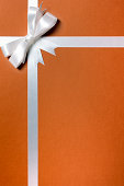 Brown paper package with white ribbon