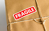 Brown paper parcel with fragile sticker