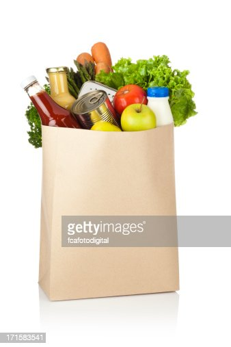 Brown paper shopping bag full of groceries on white backdrop