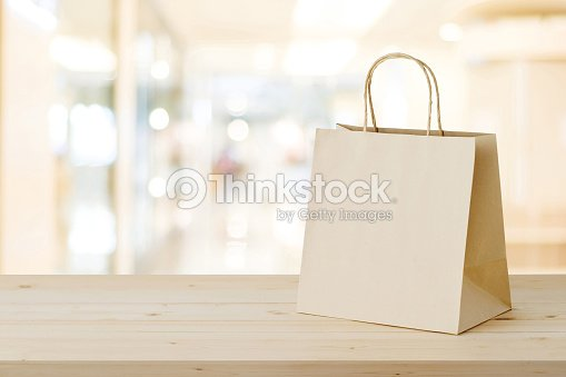 brown paper shopping bag on wood table over blurred store background