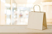 Brown paper shopping bag on wood table over blurred store background, business, template, retail, sale
