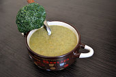 brown plate with broccoli cream soup and a sprig of fresh broccoli