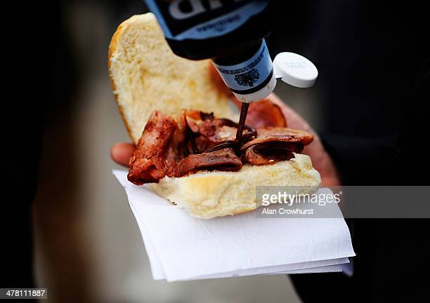 Brown sauce on a bacon breakfast bap at Cheltenham racecourse on March 12 2014 in Cheltenham England