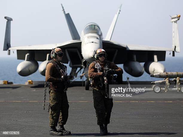 Brown shirts aka Air Wings Plane Captains wait next to a US F18 jet fighter on the flight deck of the USS Harry STrumann in the Gulf of Oman on...
