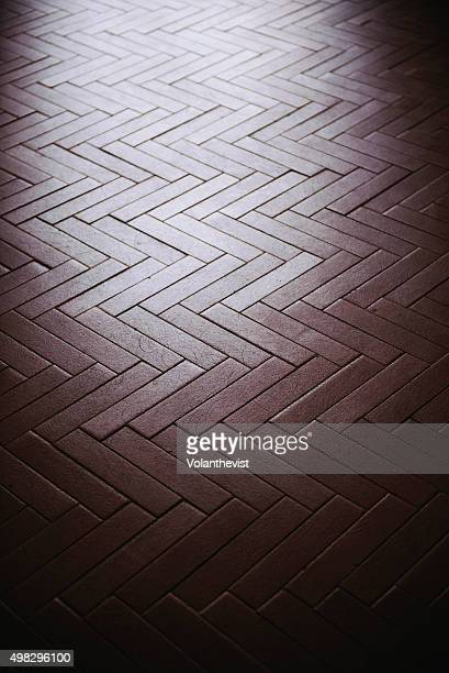 Brown tiled floor illuminated by a window