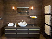 a section of a large guest's bathroom in a luxury new home with a large cabinet with drawers and a modern white basin on top. The walls are lined with wood-design ceramic tiles and the floor has large