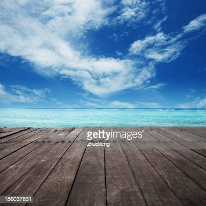 Brown wooden platform under cloudy blue sky : Stock Photo