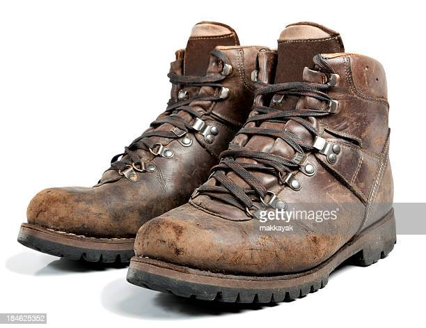 Brown worn hiking boots on white background
