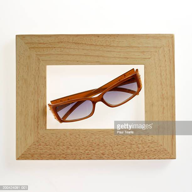 Brown-framed spectacles in picture frame, close up