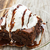 Homemade brownies with ice cream on top and chocolate sauce are topping. On glass plate over wood table.