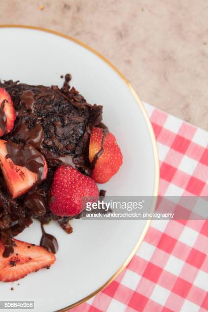 Brownie of sweet potato with strawberries and a chocolate sauce.