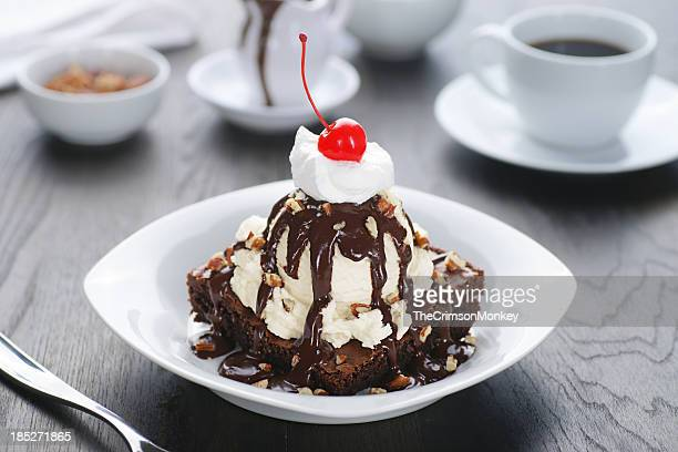 Brownie sundae with cherry on top and side cup of coffee
