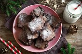 Brownies for Christmas and winter holidays. Homemade chocolate fudge brownies with milk on rustic wooden table.