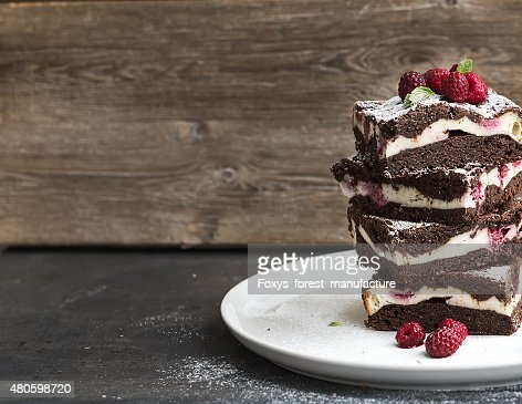 Brownies-cheesecake tower with raspberries on white plate, wooden backdrop : Stock Photo