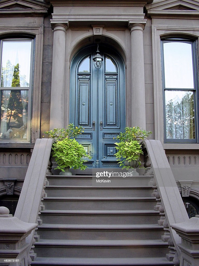 Brownstone entrance with tall wooden doors