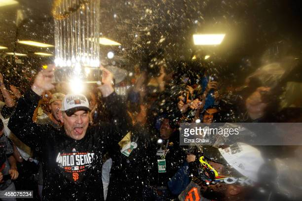 Bruce Bochy of the San Francisco Giants celebrates with The Commissioner's Trophy in the locker room after a 32 win over the Kansas City Royals in...