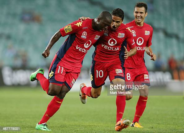 Bruce Djite of Adelaide celebrates scoring a goal with team mates Isaias Sanchez and Marcelo Carrusca during the round 18 ALeague match between...