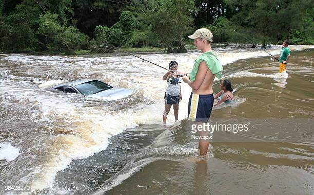 Bruce Dyball and Charlie Barden fishing at the spot where a car was swept off Lees Crossing at Dayboro in Queensland during the recent floods
