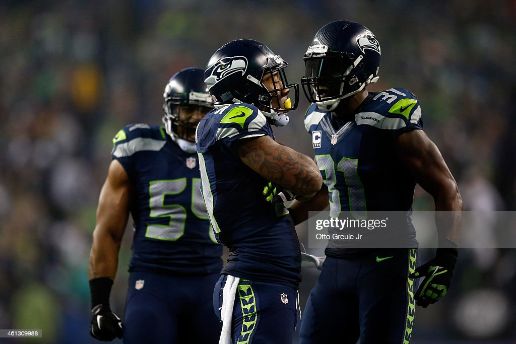 Bruce Irvin and Kam Chancellor of the Seattle Seahawks celebrate a defensive play against the Carolina Panthers during the 2015 NFC Divisional...