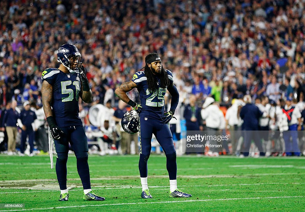 Bruce Irvin #51 and Richard Sherman #25 of the Seattle Seahawks react after losing to the New England Patriots during Super Bowl XLIX at University of Phoenix Stadium on February 1, 2015 in Glendale, Arizona. The Patriots defeated the Seahawks 28-24.