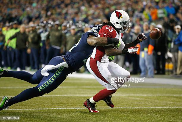 Bruce Irvin of the Seattle Seahawks breaks up a pass intended for Chris Johnson of the Arizona Cardinals during the first quarter of a game between...