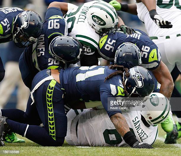 Bruce Irvine Jason Jones and Leroy Hill of the Seattle Seahawks sack quarterback Mark Sanchez along with Bilal Powell both of the New York Jets in...